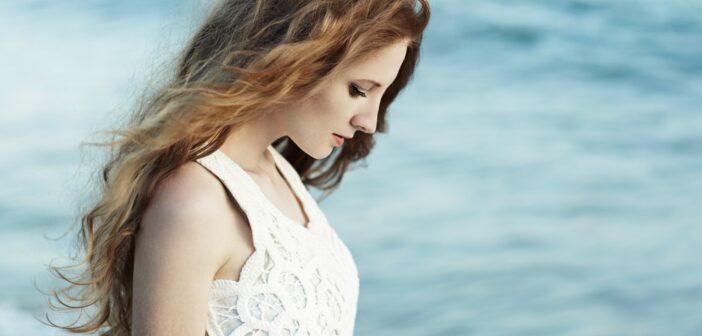 Kvinnlig modell med rött hår vid havet